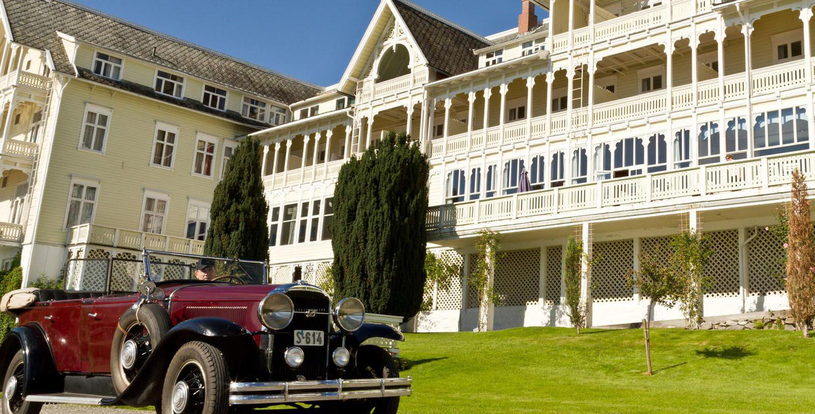 Image of Hotel Exterior with Historic Car Kviknes Hotel, 1752, Member of Historic Hotels Worldwide, in Balestrand, Norway, Special Offers, Discounted Rates, Families, Romantic Escape, Honeymoons, Anniversaries, Reunions