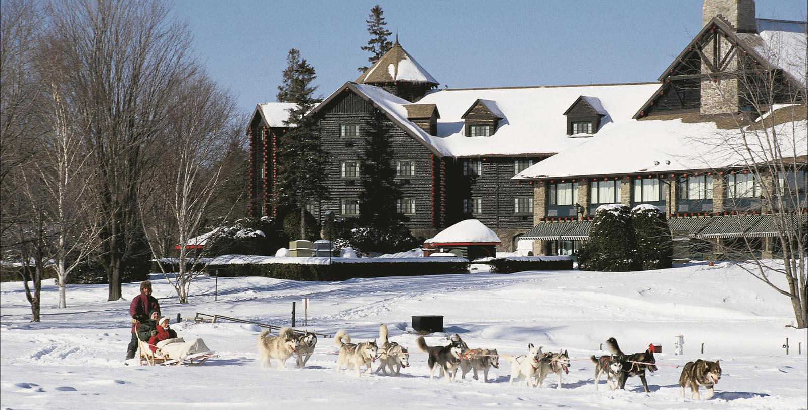 Image of Hotel Exterior with Guests Dogsledding Fairmont Le Château Montebello, 1930, Member of Historic Hotels Worldwide, in Montebello, Quebec, Special Offers, Discounted Rates, Families, Romantic Escape, Honeymoons, Anniversaries, Reunions