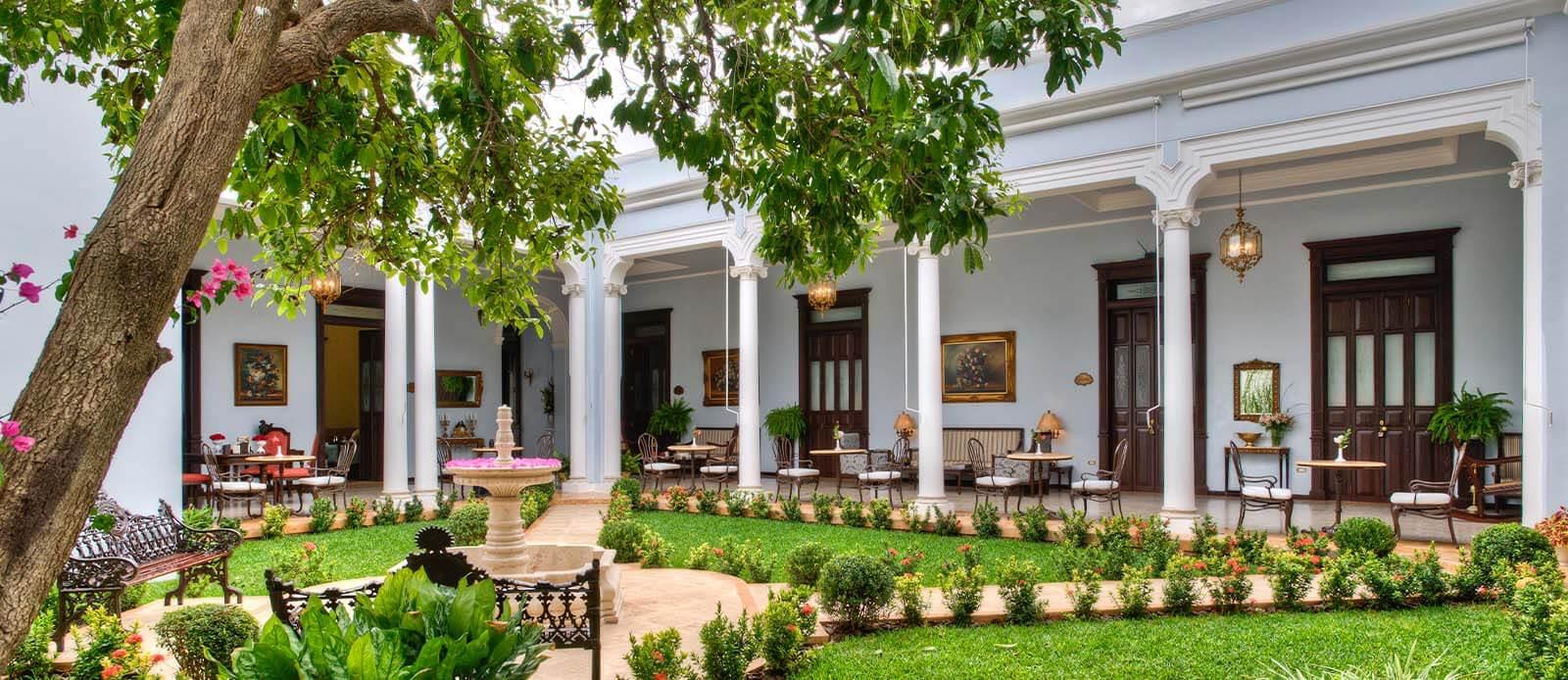 Daytime garden and courtyard of Casa Azul Hotel Monumento Historico in Merida, Mexico.