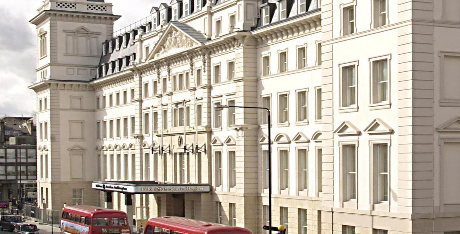 Daytime exterior of the Hilton London Paddington in London, England with double decker buses.