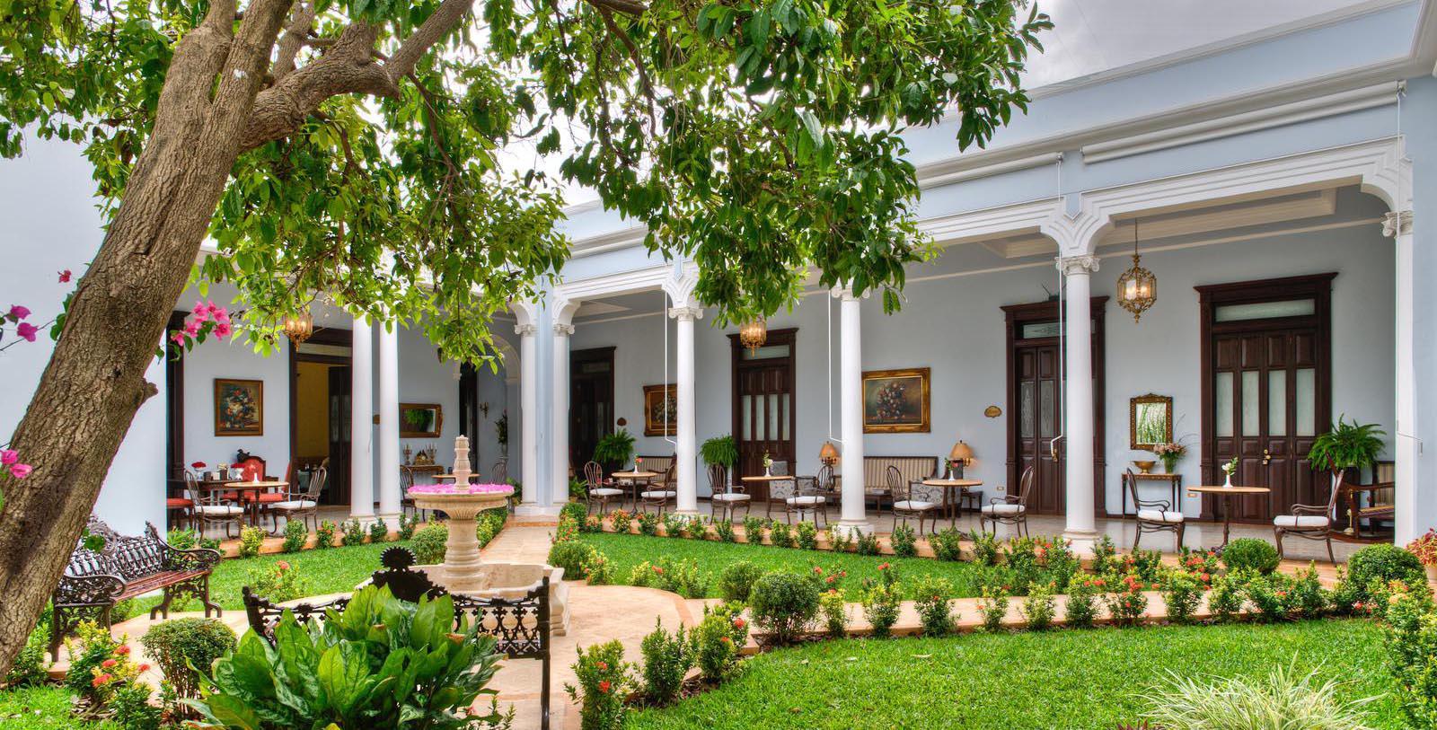 Daytime courtyard and gardens at Casa Azul Hotel Monumento Historico in Mexico.