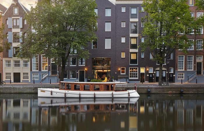 Daytime exterior of Pulitzer Amsterdam with boat and river located in the Netherlands.
