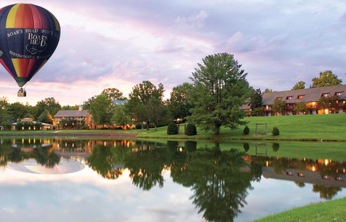 Exterior of the Boar's Head Resort in Charlottesville, Virginia, with hot air balloon and lake.
