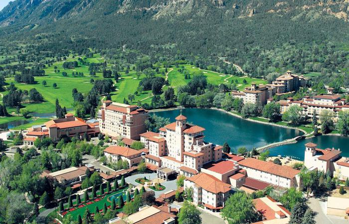 Daytime aerial of The Broadmoor in Colorado Springs with mountains.