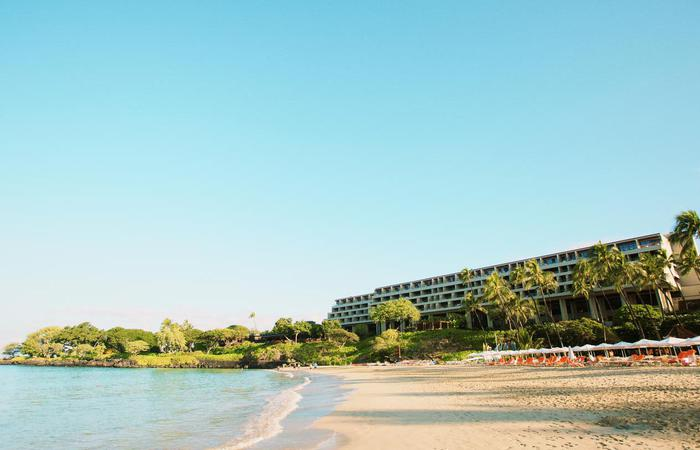 Beach and exterior daytime of the Mauna Kea Beach Hotel in Hawaii.