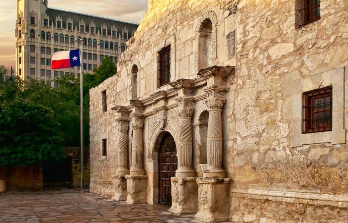 Exterior view of The Alamo with The Emily Morgan San Antonio - a DoubleTree by Hilton Hotel in the back.
