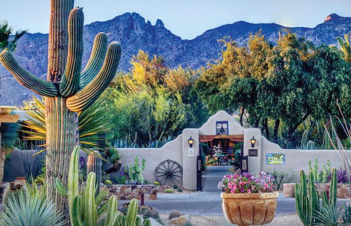 Entrance to the Hacienda Del Sol Guest Ranch Resort in Tucson, Arizona with cactus and mountains.