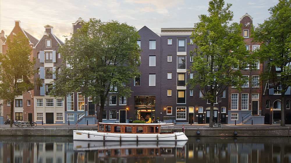 Daytime exterior of Pulitzer Amsterdam with boat and river in the Netherlands.